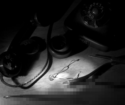 Black and White photo of the receiver of an old rotary dial telephone being cracked open and hacked into